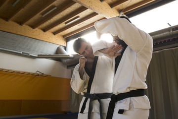 Two men wearing white kimonos and fighting hard while practicing hapkido.
