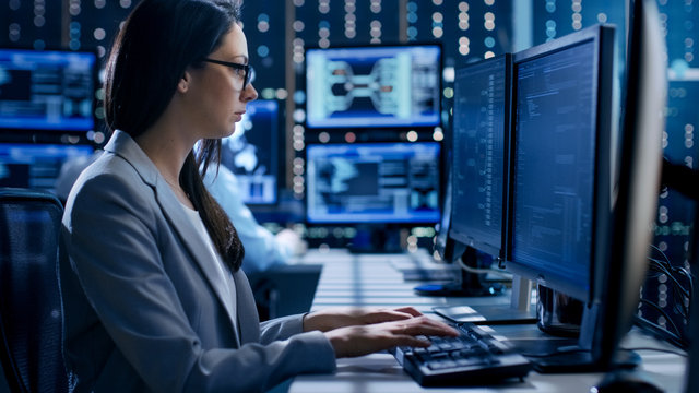 Female Engineer Controller Observes Working of the System. In the Background People Working and Monitors Show Various Information.