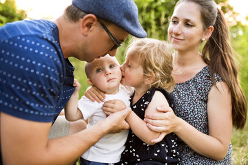 Young family with little children in sunny summer nature