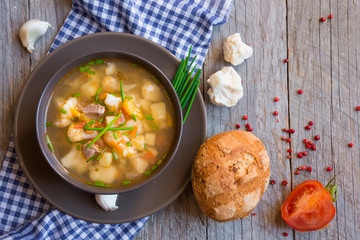 Vegetable soup with bread on wood