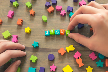 Pure hands of a beautiful young girl neatly lay out the word Jesus from bright colored alphabetic cubes on a brown wooden table