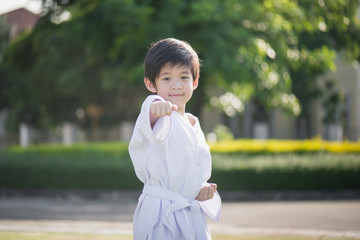 Cute Asian child in white kimono during training karate in summer outdoors