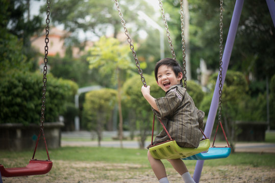 Asian child in kimono playing on swing i