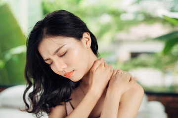 Young asian woman suffering from neck pain while sitting on bed at home