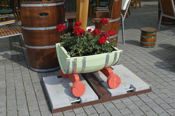 wooden stand with red flowers in the park.