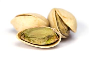 Three salt pistachio nuts isolated on white backround close up