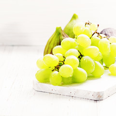 Green grapes with ripe figs fruit on white wooden background.