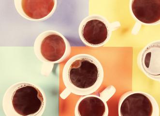 много кружек с напитком стоит на цветном фоне