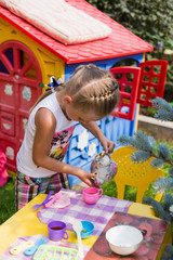 Sweet girl playing on the lawn. Girl pouring tea into cups summer day. Girl playing baby dishes