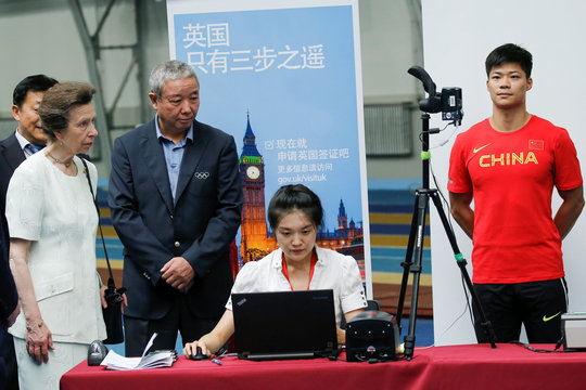 Britain's Princess Anne watches a Chinese athlete provide his biometrics for his visa application at a mobile processing station at the National Athletics Training Centre in Beijing