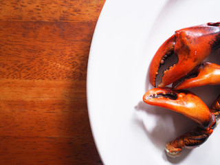 Top view picture of boiled freshwater crab claws on white plate above wooden table.