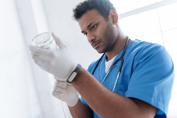 Attentive dark-skinned doctor looking at bottle with medicine