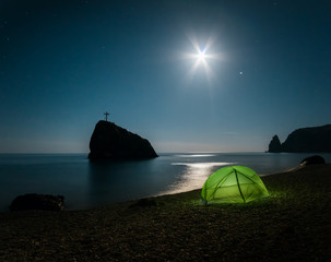 Tent on the beach with rocks and a night sky with stars
