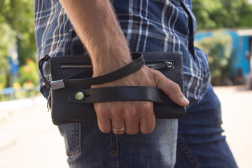 A guy in jeans and a shirt with a purse on his hand