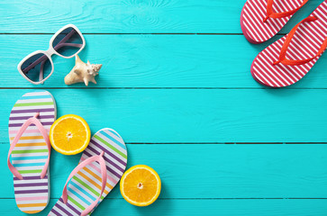 Flip flops, sunglasses and oranges on blue wooden background. Top view and copy space
