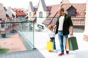 father and son holding shopping bags while walking on balcony of shopping mall