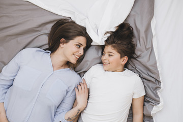 Overhead photo of mother and son lying on bed and smiling.
