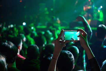One of fans photographing rock or pop singer on stage