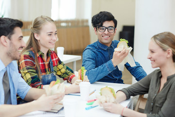 Group of happy buddies with sandwiches having talk after lesson at lunch break