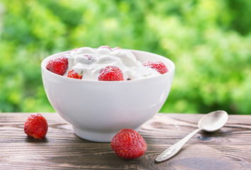 .Yogurt with strawberries in a white bowl on a wooden table in the garden.