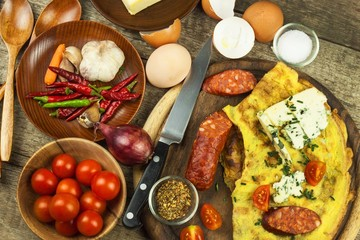 Delicious stuffed omelette on a wooden board. Fried egg omelette with cherry tomatoes, garlic and chili peppers. Nutritious breakfast.