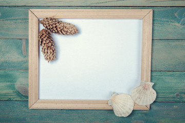 Blank photo frame with pine cones and sea shells