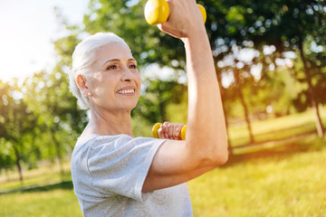 Cheerful smiling aged woman doing sport exercises in the park