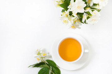 Jasmine flowers and cup of green tea on white. Top view and concept. Teatime.
