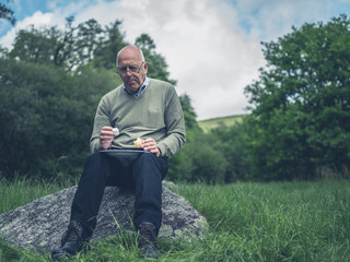 Senior man having a picnic for one on a rock