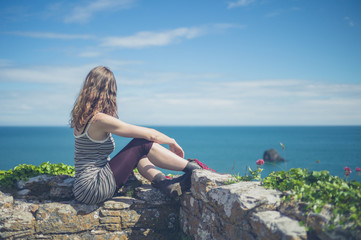 Woman relaxing on wall by the sea