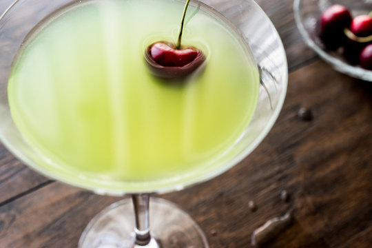 Appletini Cocktail with cherry on wooden surface.