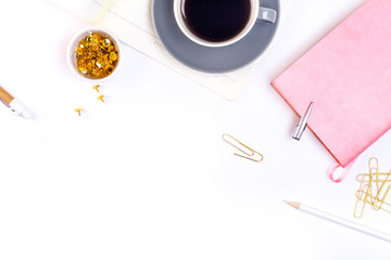 Workplace mockup with pink leather notebook and cup of coffee on white background top view. Flat lay with copy space. Feminine working style concept.