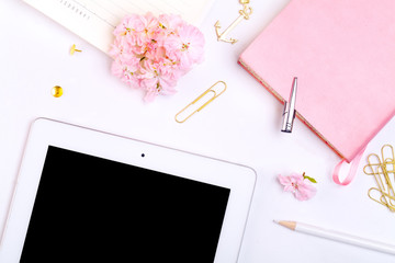 Workplace mockup with pink leather notebook, glasses, white tablet and golden accessories on white background top view. Flat lay with copy space.  Feminine working style concept.