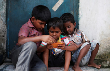 Children play a game on a mobile phone at slum area in New Delhi