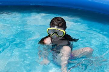 girl in swim mask in backyard pool