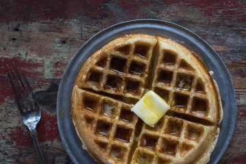 top view waffles with butter and syrup and fork