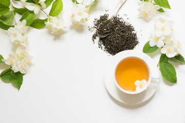Jasmine dry green tea leaves with jasmine flowers and cup of tea on white background. Copy space and top view. Teatime.