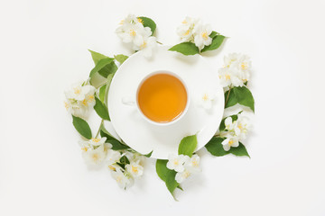 Jasmine flowers around cup of green tea on white background. Top view and concept.