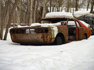 Old red car rusts under a layer of snow