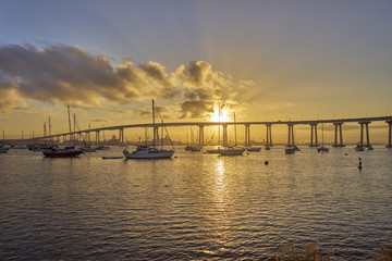 boats under and beautiful sunrise over the Coronado Bridge, San Diego California