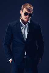 Fashion young man in sunglasses, luxury suit on dark background