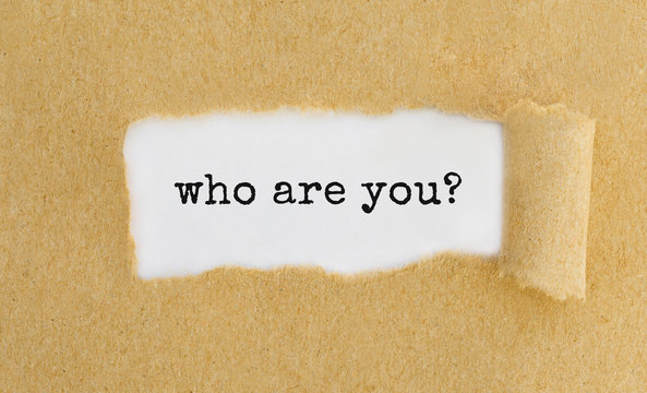 Text who are you appearing behind ripped brown paper