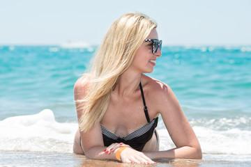 Beautiful young woman in bikini lying and sunning on the beach