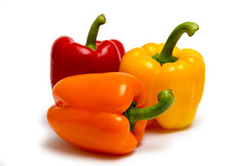 red, orange and yellow peppers isolated on white background