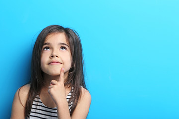Beautiful little girl in dress on blue background