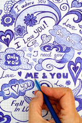 Woman hand with ballpoint pen draws love doodles messages on checkered paper.