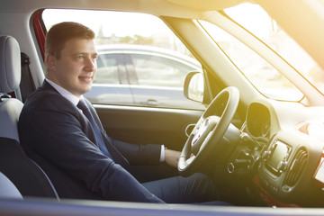 Businessman sitting in his car in a highway jam. Looking in the distance while in traffic. Suit and tie businessman sitting in his automobile.