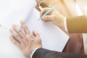 Closeup of a man's hand filing a blank paper form on a clipboard. Modern businessman standing in a parking lot leaning on a hood of the car. Lens Flare in the background.