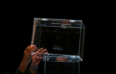 A man holds a ballot box after a meeting about the terms and conditions of the independence referendum in Barcelona