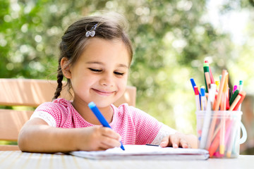 Little Girl Drawing Picture Outdoors In Summer